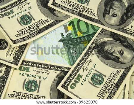 Heap of dollar bills around an euro banknote - stock photo