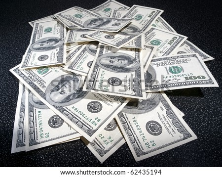 heap of dollars greenback in dark background - stock photo