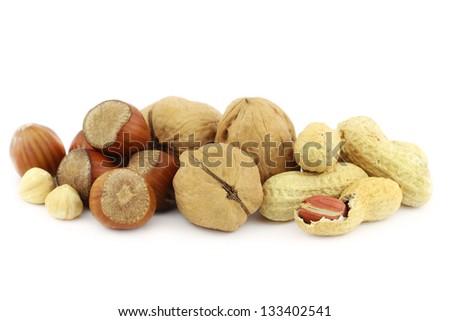 Heap of dried nuts - hazelnuts, walnuts and peanuts - on white background - stock photo