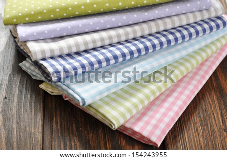 heap of  fabrics on wooden table closeup - stock photo
