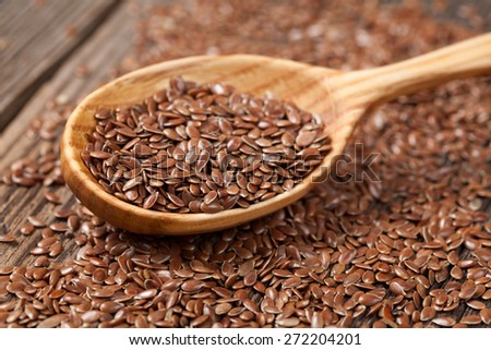 Heap of flax seeds super food nutrition in wooden spoon. Flax seeds are rich of omega fat. - stock photo