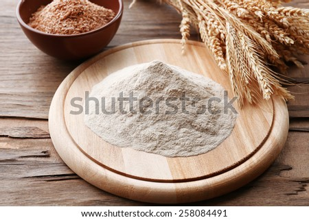 Heap of flour on cutting board with ears on wooden table - stock photo