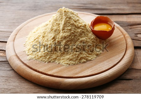 Heap of flour on cutting board with egg on wooden table - stock photo