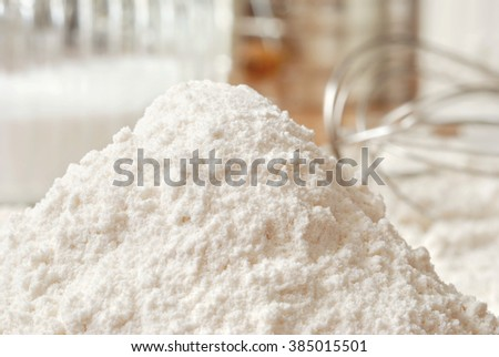 Heap of flour with whisk and baking ingredients in background.  Closeup with shallow dof.  Baking concept. - stock photo