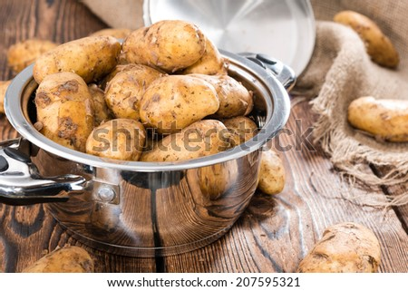 Heap of freh Potatoes on wooden background (close-up shot)