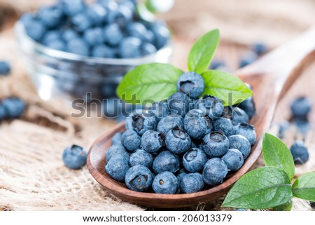 Heap of fresh Blueberries on a Wooden Spoon (close-up shot) - stock photo