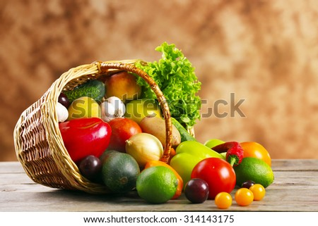 Heap of fresh fruits and vegetables in basket on wooden table close up - stock photo