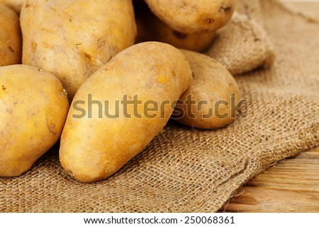 heap of fresh potatoes on burlap sack - stock photo