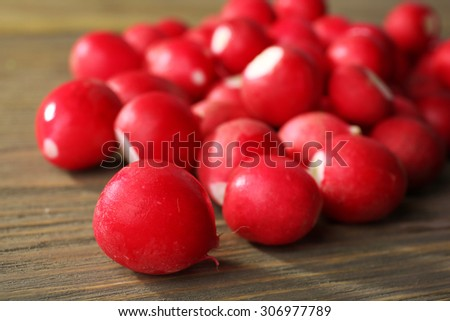 Heap of fresh radishes on wooden table close up background - stock photo