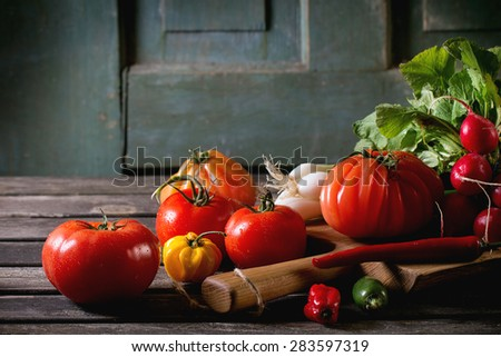Heap of fresh ripe colorful vegetables tomatoes, chili peppers, green onion and bunch of radish on wooden chopping board over old wooden table. Dark rustic atmosphere - stock photo