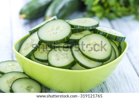 Heap of fresh sliced Cucumbers on an old wooden table - stock photo