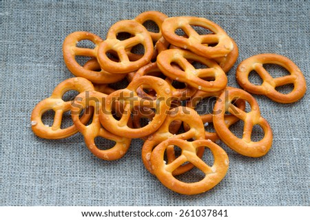 Heap of fresh Wheat salt pretzels on hessian linen fabric cloth - stock photo