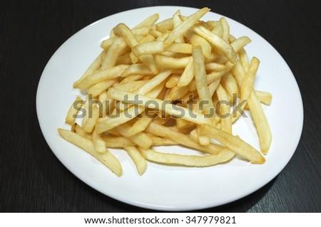 Heap of fried potato chip sticks on white dish - stock photo