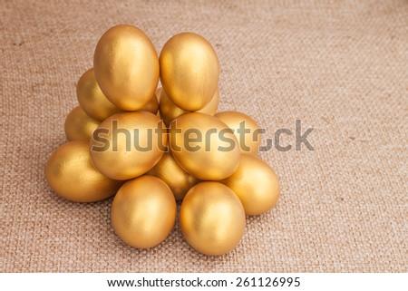 Heap of golden easter egg on brown sack background - stock photo