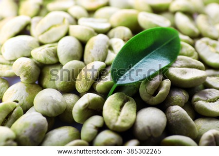 Heap of green coffee beans with leaf close up - stock photo