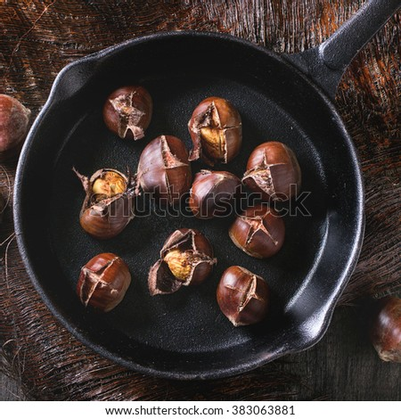 Heap of grilled edible chestnuts in cast iron skillet over dark palm crust. Flat lay. Square image - stock photo