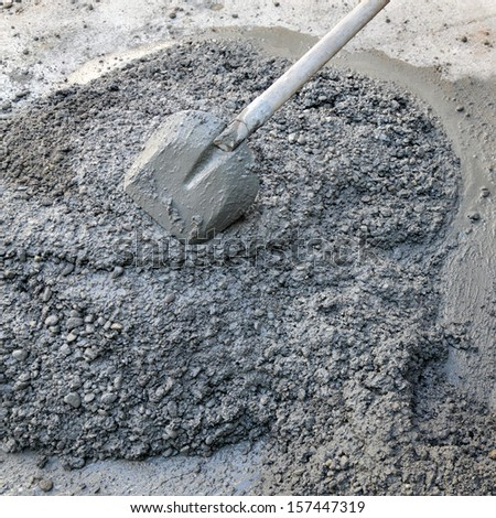 Heap of hand mixed concrete with shovel - stock photo