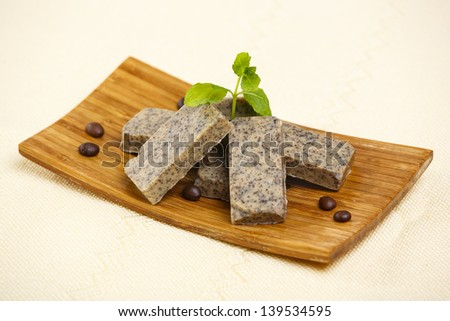 Heap of handmade flavored soap bars with coffee beans and green lavender leafs on wooden stand. - stock photo