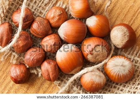 Heap of hazelnuts healthy seasonal vegetarian snack in nutshell natural food on wooden background - stock photo