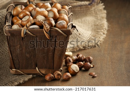 Heap of hazelnuts in basket with burlap on wood. - stock photo