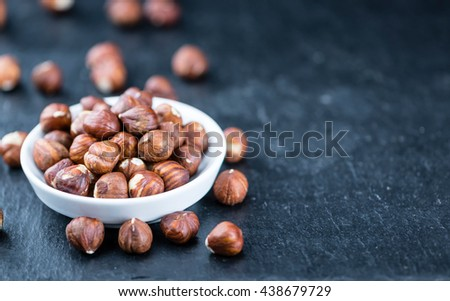 Heap of Hazelnuts (selective focus) on vintage background (close-up shot)