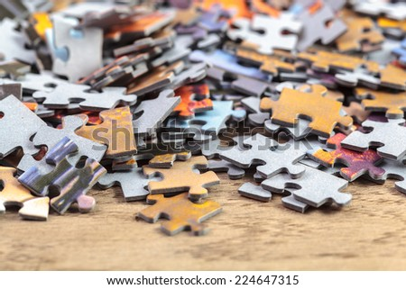 Heap of jigsaw puzzle pieces on a table. Shallow depth of field - stock photo