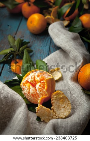 Heap of mandarins on a wooden table, one mandarin is peeled - stock photo
