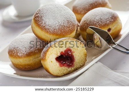 heap of marmalade filled bismarck donuts on white plate - stock photo