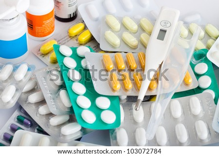 Heap of medical supplies, pills, tablets, capsules, and thermometer.