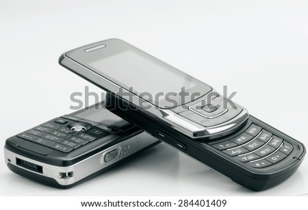 Heap of mobile phones on light background. Shallow depth of field. - stock photo