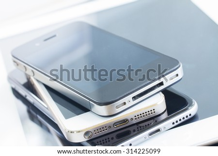 heap  of modern glossy electronical devices close up - technology concept - stock photo