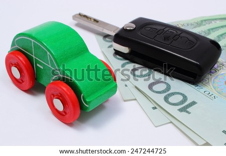 Heap of money, old wooden green toy car and key car. Isolated on white background
