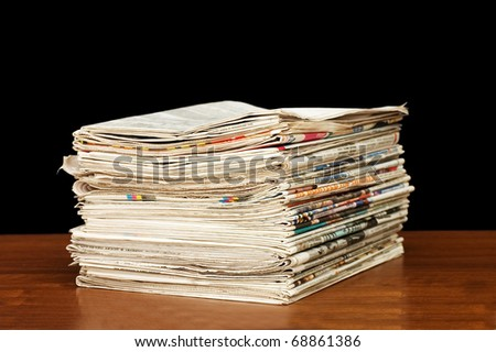 Heap of newspaper on a wooden table - stock photo