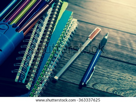 Heap of notebook with pens on wooden table under light in vintage style