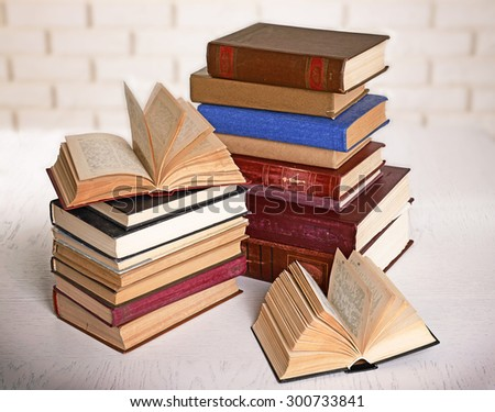 Heap of old books on brick wall background - stock photo
