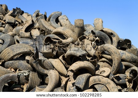 Heap of old muddy chopped up tires are piled in a recycling yard waiting to be remanufactured in to new products. - stock photo