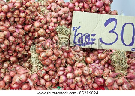 Heap of onions dry for sale, price 30 Baht per kilogram  in Thai language.