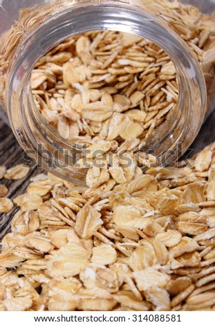 Heap of organic oatmeal, oat flakes spilling out of glass jar on wooden background, concept for healthy eating and nutrition