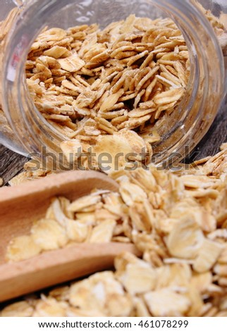 Heap of organic oatmeal, oat flakes spilling out of glass jar on wooden background, concept of healthy eating