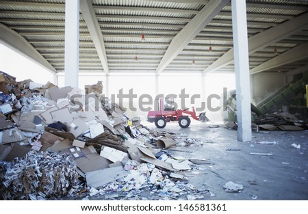 Heap of paper waste with digger truck in background at recycling plant - stock photo
