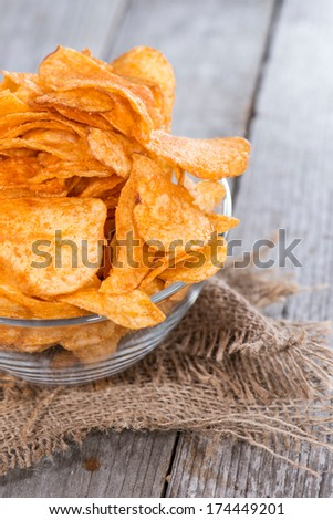 Heap of Paprika Potato Chips on rustic background - stock photo