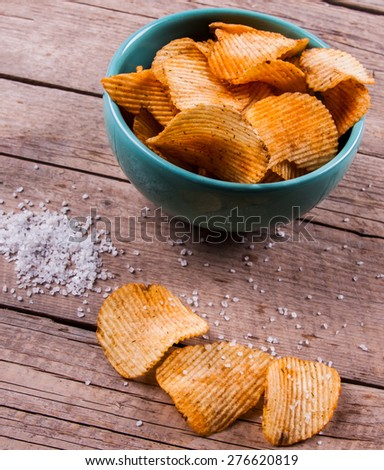 Heap of Paprika Potato Chips on rustic background - stock photo