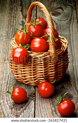 Heap of Perfect Ripe Cherry Tomatoes with Stems in Wicker Basket isolated on Rustic Wooden background - stock photo
