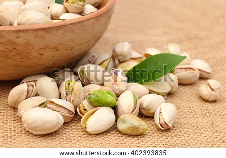 Heap of pistachios nuts isolated and wooden bowl on the burlap - stock photo
