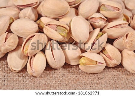 Heap of pistachios on a sacking background - stock photo