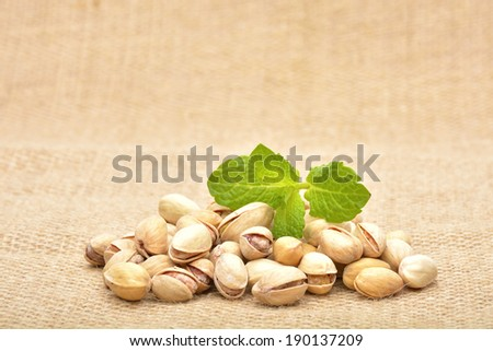 Heap of pistachios on old canvas
