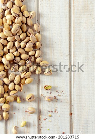 Heap of pistachios on the wooden table from above with blank space on right side - stock photo