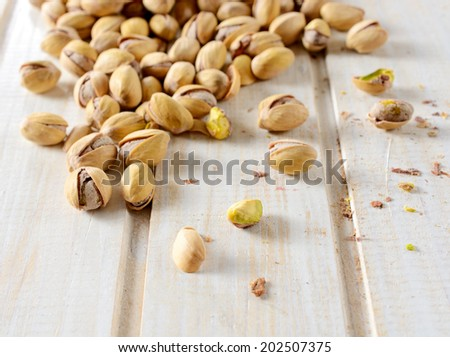 Heap of pistachios on the wooden table.Selective focus on the front pistachio  - stock photo