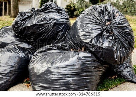 Heap of plastic trash bags on curb waiting for sanitation pickup - stock photo