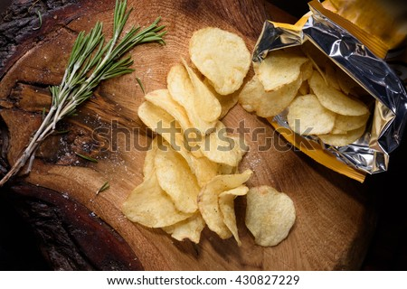 Heap of potato chips with rosemary over wooden background. View from above. - stock photo